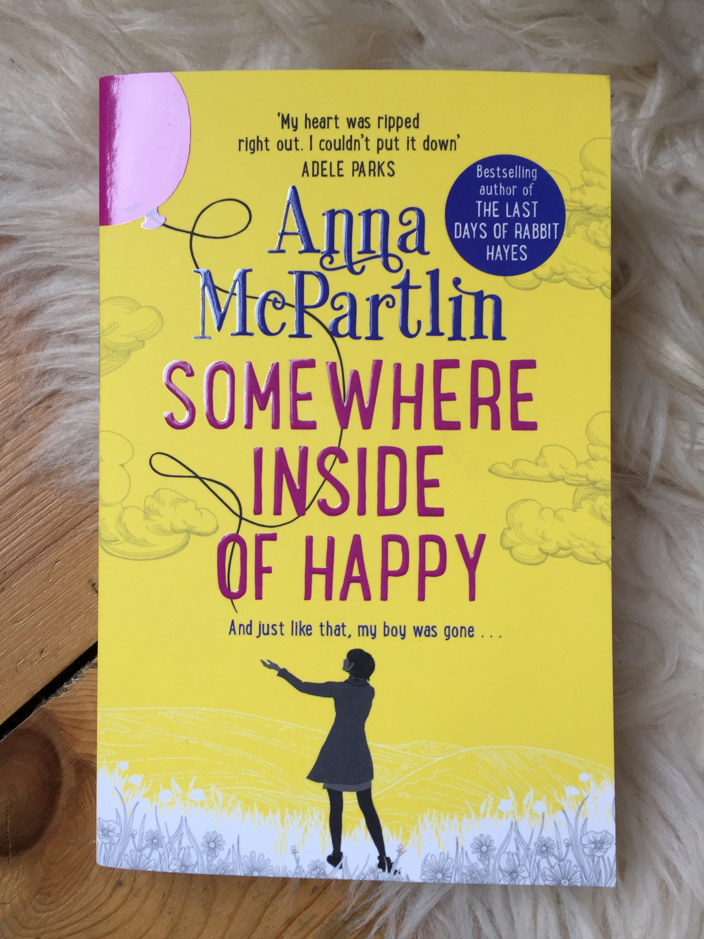 A paperback copy of Somewhere Inside of Happy