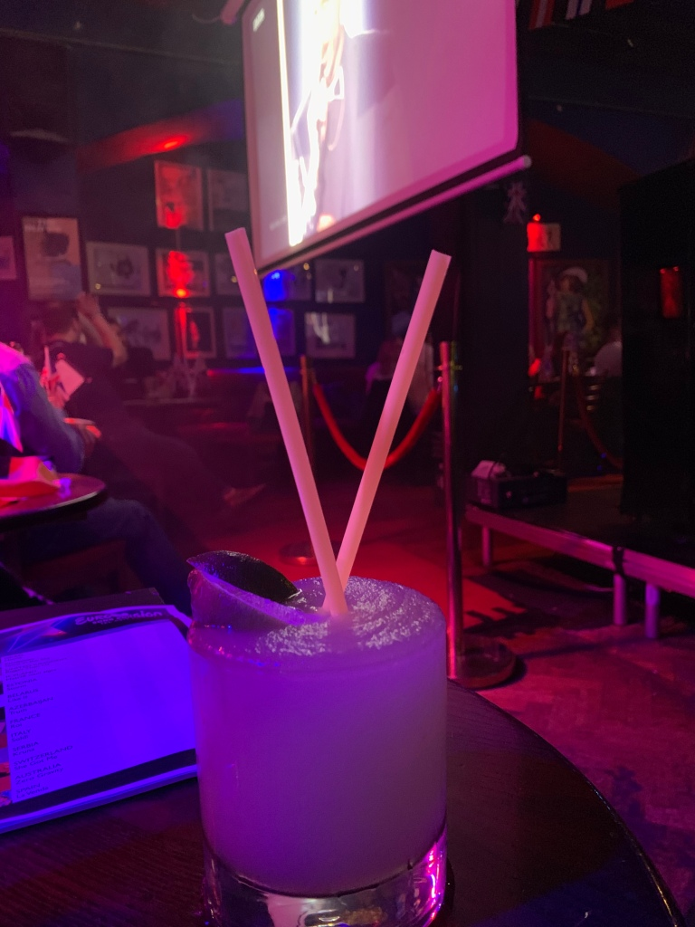 Frozen Margarita with a projector showing Eurovision in the background in a club