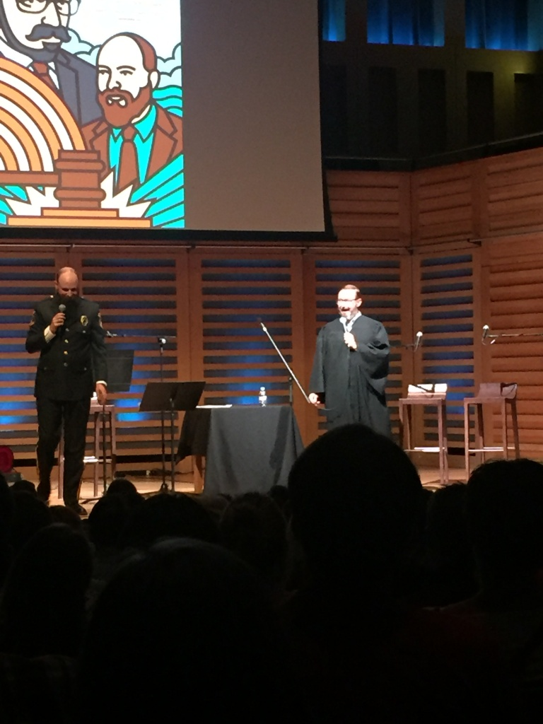 John Hodgman on stage in a judge costume