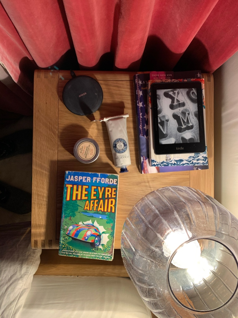 Bedside table from above, featuring hand cream, a copy of the Eyre Affair and a pile of books