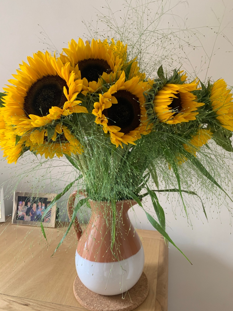 A large bunch of sunflowers in a jug