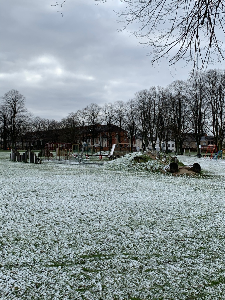 Snowy grass and play equipment under a heavy grey sky