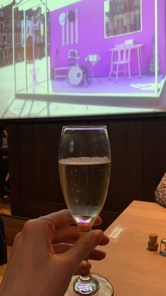 A glass of prosecco in front of a large screen showing Eurovision Semi final 2
