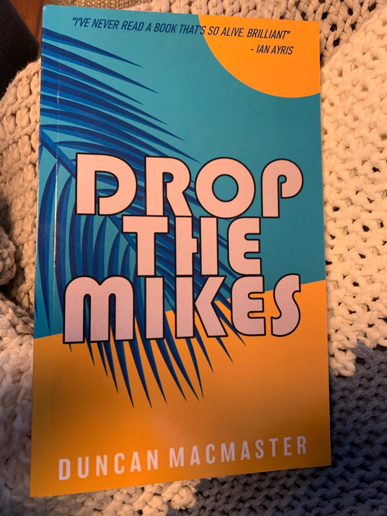 Paperback copy of Drop the Mikes